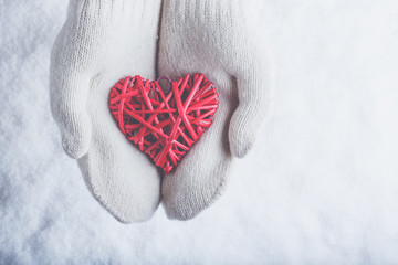 Female hands in white knitted mittens with entwined vintage romantic red heart on snow background. Love and St. Valentine concept