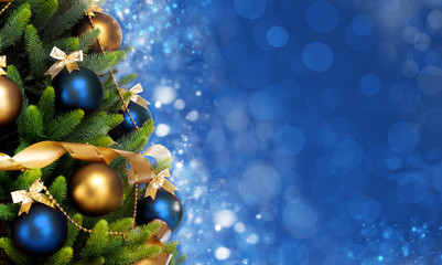 Magically decorated Fir Tree with balls, ribbons and garlands on a blurred Christmas blue shiny and sparkling background.