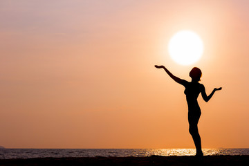 Female silhouette standing on sunset sea background, back lit