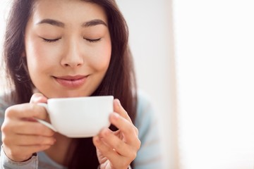 Asian woman relaxing on couch with coffee