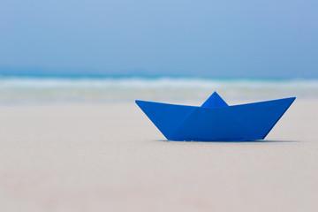 Blue paper boat on white sand seashore, blue sea background