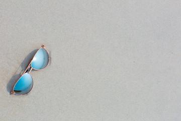 Sunglasses lying on the beach, white sand