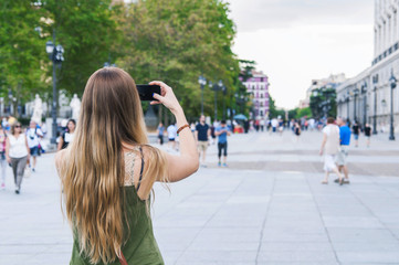 Young blonde woman sightseeing and taking photos with her smartphone in Madrid, Spain.