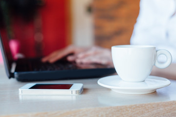 Woman with laptop, cup of coffee and mobile phone on the table