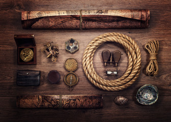Wall Mural - Overhead view of pirate or sailor gear laid out for a backpacking trip on a old wood floor. Items include, rope, compass, money, map, binoculars, hourglass, sextant , shell. Stories background.