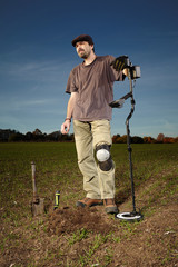Autumn day in field with metal detector