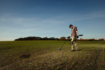 Obraz Exploring autumn field with metal detector - fototapety do salonu