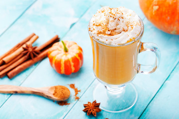 Pumpkin smoothie, spice latte with whipped cream. Turquoise wooden background.