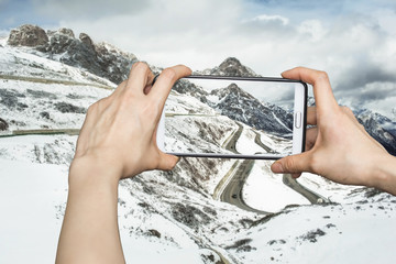 Girl taking pictures on mobile smart phone in snow mountain,Chin