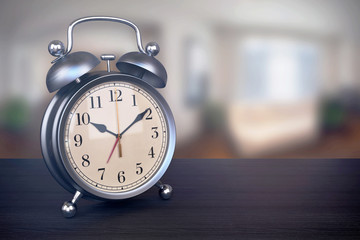 Retro alarm clock on bedside table in bedroom