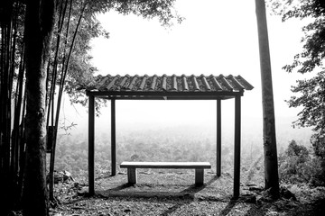 Black and White and Silhouette of Small pavilion and bench at side of way