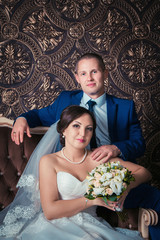 Studio portrait of happy smiling bride and groom sitting on the brown sofa on their wedding day