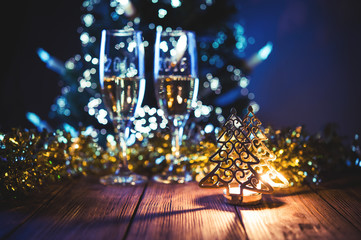 A decorated christmas table with champagne glasses and christmas tree in background. Selective focus.