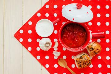 Ukrainian national cuisine , red borscht with sour cream , herbs , garlic and pumpushki on a wooden background