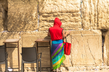Unidentified tourist in a bright red jacket and colorful female scarf , harboring legs in shorts at the Western Wall