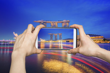 Girl taking pictures on mobile smart phone in Singapore city