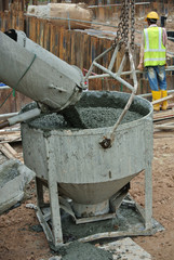 A concrete bucket receiving concrete from concrete truck