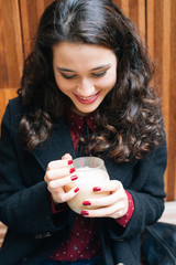 Happy woman having a coffee with milk