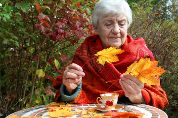 Happy Senior Woman Holding Autumn Leaves