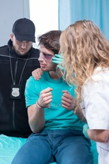 Injured man with policeman and doctor