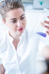 Woman scientist holding glass utensil