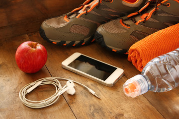 fitness concept with mobile phone with earphones, towel, apple and sport footwear over wooden background. retro filtered