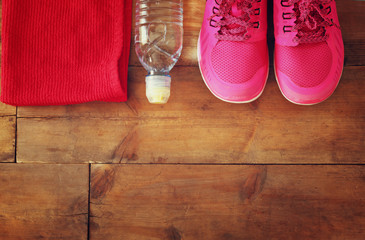 fitness concept with bottle of water, towel and woman sport footwear over wooden background