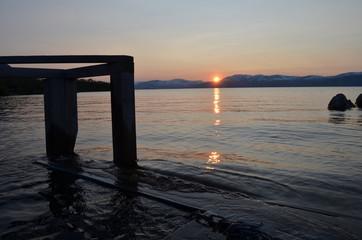 Wooden jetty in lake Torneträsk, Abisko, with midnight sun
