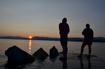 Two silhouets of people standing on pier in Swedish lake with midnight sun
