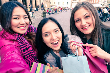 Three young women taking selfie outdoor - Smart studends having fun by mobile phone - Happy smiling tuorists girls with shopping bags doing funny facial expressions - Friendship and technology concept