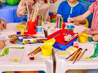 Kids hands holding colored paper and glue on table in kindergarten