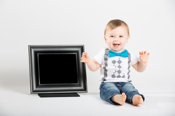 a cute 1 year old baby sits next to a blank black picture frame in a white studio setting. The boy is extremely excited with hands in the air. dressed in Tshirt, jeans, suspenders and blue bow tie