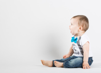 a cute 1 year old stands in a white studio setting. The boy is yelling with an open mouth. He is dressed in Tshirt, jeans, suspenders and blue bow tie
