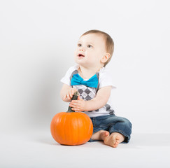 a cute 1 year old sits in a white studio setting with a pumpkin. The boy looks off camera while holding pumpkin stem. He is dressed in Tshirt, jeans, suspenders and blue bow tie