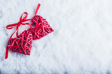 Two beautiful vintage red hearts tied together with a ribbon on a white snow background. Love and St. Valentines Day concept.