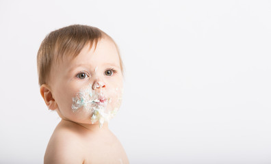 a cute 1 year old sits in a white studio setting. Close up of a baby with a face full of cake and frosting. He is only dressed in a white diaper