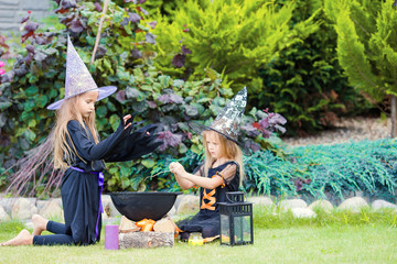 Wall Mural - Adorable little witches have fun outdoors on Halloween. Trick or treat