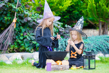 Wall Mural - Happy little witches have fun outdoors on Halloween. Trick or treat
