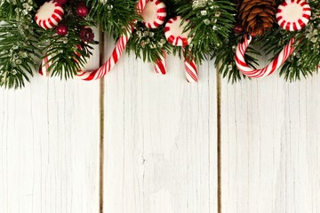 Christmas top border of branches and candy canes against a white wood background