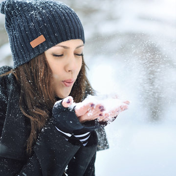 Young beautiful woman blowing snow in winter
