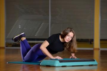 Sporty girl doing push-ups on platform for an aerobics step