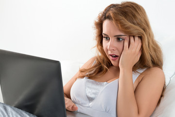 Young shocked woman reading something at laptop