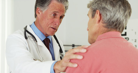 Senior doctor talking to elderly patient with hand on shoulder