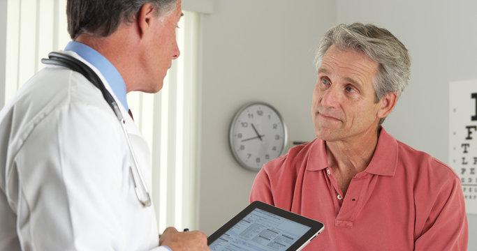 Senior doctor asking elderly patient questions