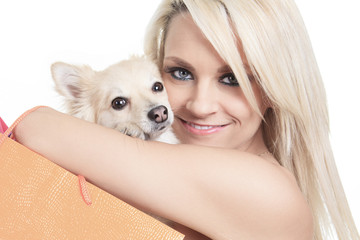 Beautiful woman holding dog in studio