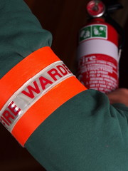 Fire warden with a reflective high visibility identification patch holding a fire extinguisher, Melbourne 2015