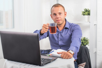 Businessman working in office, sitting at  table holding a cup and looking straight