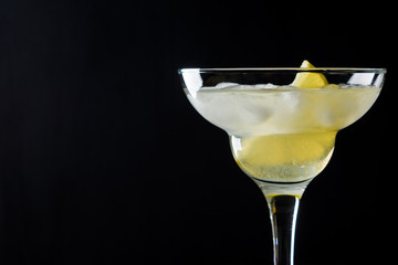 Cocktail margarita with lemon on black background
