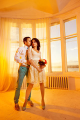 Beautiful young wedding couple is standing at bright sunny window