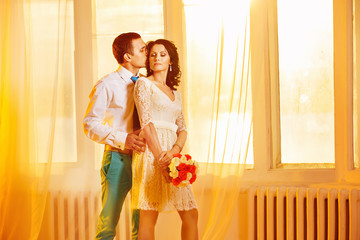 Beautiful young couple is kissing at golden sunset window